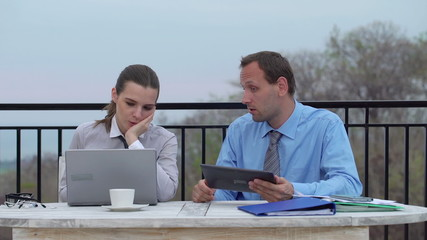 Boss with tablet yelling at businesswoman by the table on terrac
