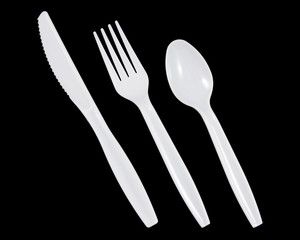 White plastic knife, fork and spoon on black background.