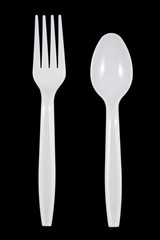 White plastic fork and spoon on black background.