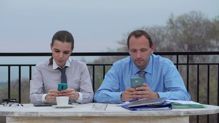 Business couple texting, using smartphones by the table on terra