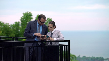 Business couple talking over smartphones on terrace