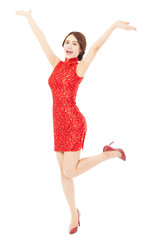 happy asian young woman with cheongsam raising hands .
