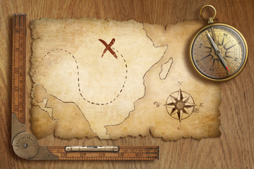 aged treasure map, ruler and old gold compass on wooden table to