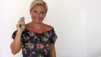 woman with remote control looking at the camera and smiling