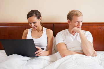 Bored husband and wife with laptop