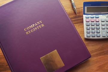 Company Register documents with pen and calculator