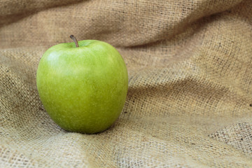 Granny Smith apple on the burlap background. Copy paste