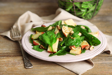 Green salad with apples, walnuts and cheese on wooden