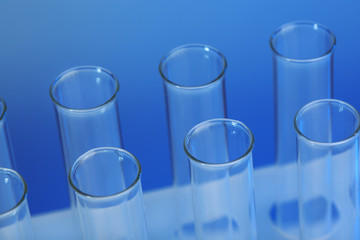 Empty test-tubes on blue background closeup
