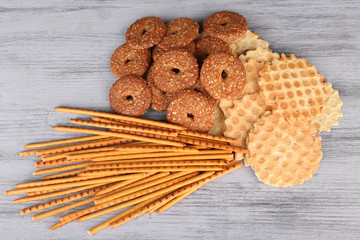 Biscuits and sticks scattered on wooden background