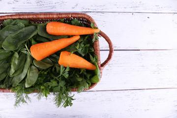 Carrots and sorrel in rectangular wicker basket