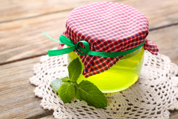 Homemade mint jelly in glass jar, on wooden background