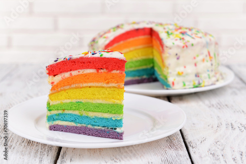 Delicious rainbow cake on plate on table on light background