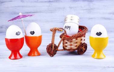 Eggs in egg cups and on bicycle on grey wooden background