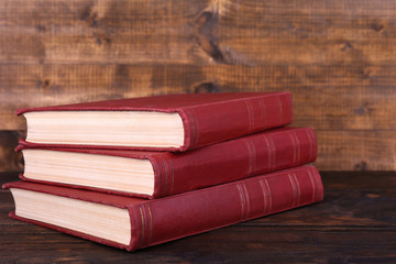 Books on wooden table on wooden wall background
