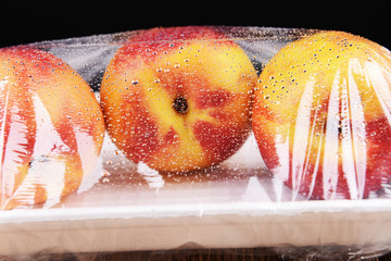 Peaches packed in food film on table close-up