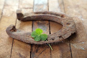 Old horse shoe,with clover leaf, on wooden background