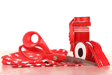 Ribbons with scissors and fabrics on light background