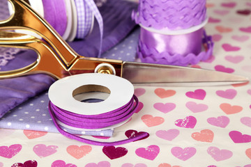 Ribbons with scissors and fabrics on bright background