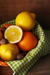 Lemons on napkin in basket on wooden background