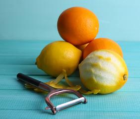 Lemons and oranges and peeling knife on blue wooden background