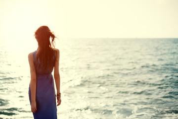 beautiful girl in blue dress near the ocean