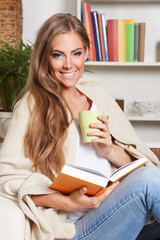 Beautiful woman having a cup of drink while reading