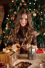 Beautiful young woman wrapping a christmas gift