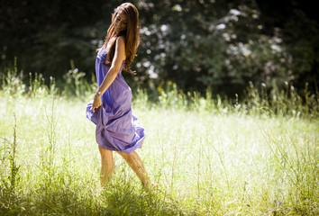 Attractive female model in blue dress.She walking trough meadow.