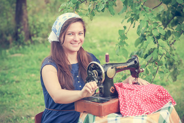 Happy woman with vintage hand sewing machine