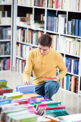 Young man looking at the books in a library.