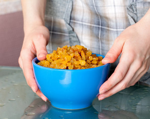 Woman's hands holding a bowl of raisins