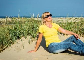 Frau mit Sonnenbrille am Sandstrand