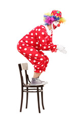 Male clown preparing to jump off a chair