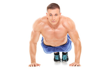 Athletic man doing pushups and looking at camera
