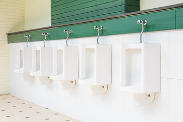 A row of urinals in tiled wall in a public restroom