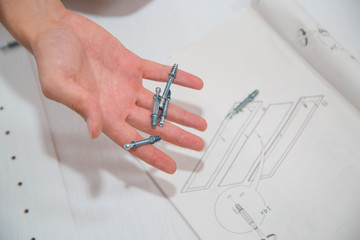Screw-bolts and nuts in hand