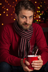 Christmas - smiling man holds hot drink or cocoa cup