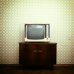 Retro tv with wooden case in room with vintage wallpaper and par