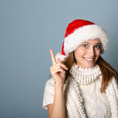 Portrait of attractive cheerful girl in Santa's hat pointing wit