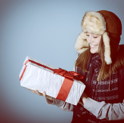 Portrait of attractive cheerful christmas girl in winter hat hol