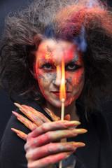 Hexe hält einen brennendes Strichholz mit Qualm