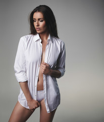 Attractive female model posing in unbuttoned shirt