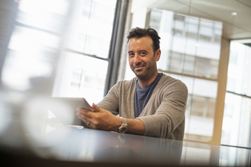 Office life. A man seated at a desk using a digital tablet.
