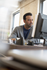 Office life. A man seated at a desk using a computer.