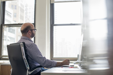 Office life. A man sitting at a desk using a computer, looking intently at the screen.