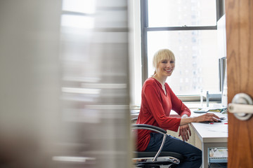 Office life. A woman seated at a desk looking at the camera and smiling.