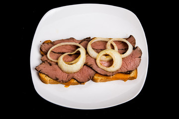 Hot Sliced Beef Sandwich with Onion Rings on Black