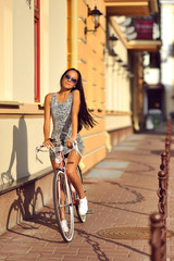 Outdoor fashion portrait of a beautiful brunette with bike