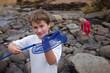 Vacation boy catching crab at river